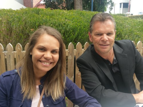 A male and female Aboriginal staff sitting and smiling